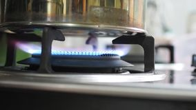 Gas stove blue fire flame heating kettle stock footage