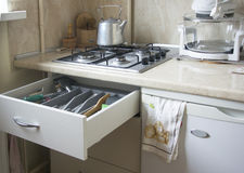 Gas stove, kettle and drawer with kitchen utensils. Stock Images