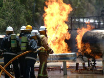 Gas tank on fire with Emergency Fire Fighters. Featuring a gas tank burning out of control in a bush fire after an emergency call Stock Images