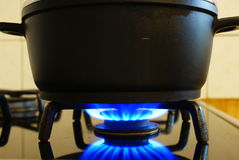 Gas under pot. Blue gas under black pot in the kitchen Royalty Free Stock Photography