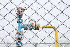 Gas valve with fence in the foreground. Stock Photo
