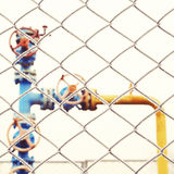 Gas valve with fence in the foreground. Stock Image