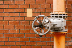 Gas valve on yellow natural gas distribution industrial pipe in front of red brick wall with copyspace Stock Images