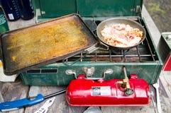 Gasa den campa ugnen och fräsabacon i småfiskpanna arkivfoto