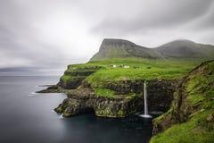 Gasadalur by och dess iconic vattenfall, Vagar, Faroe Island, Danmark exponering long arkivbild