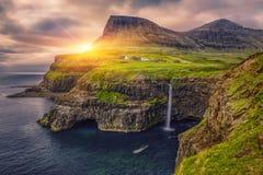 Gasadalur by och härlig vattenfall, på solnedgången, Vagar, Faroe Island royaltyfria foton