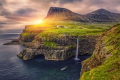 Gasadalur village and Beautiful waterfall, At Sunset, Vagar, Faroe Islands royalty free stock photos