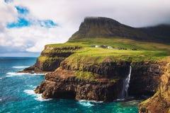 Gasadalur village and its waterfall under strong wind, Faroe Islands, Denmark