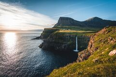 Gasadalur village and Mulafossur its iconic waterfall during summer with bluw sky. Vagar, Faroe Islands, Denmark. Rough
