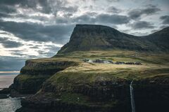 Gasadalur village and Mulafossur its iconic waterfall during sunset in summer with bluw sky. Vagar, Faroe Islands