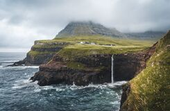 Gasadalur village and Mulafossur its iconic waterfall, Vagar, Faroe Islands, Denmark. Rough see in the north atlantic