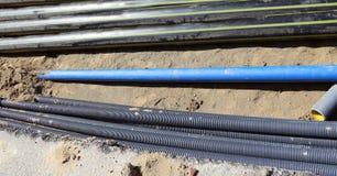 Gasdotto dentro lo scavo in constructio della strada Immagine Stock
