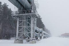 Gasdotto enorme posato lungo la via nevosa a Riga, Lettonia fotografia stock