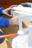 Gasgenerator schließt die Schlauchleitung von der Gasflasche an den Gaskocher an Lizenzfreie Stockfotografie