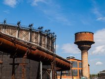 Gasholder and water tower in the industrial zone Royalty Free Stock Photo