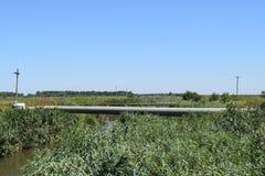 Gasledningen till och med den lilla floden Arkivbild