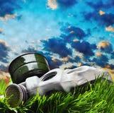 Gasmaske, die auf dem Gras gegen den rauchigen Himmel liegt Stockfotografie