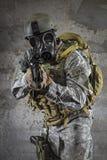 Gasmaskermilitair die geweer streven stock afbeelding