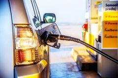 A gasolina de bombeamento abastece-se em um carro em um posto de gasolina trabalhador no elevador de bens; o azul pintou; porta f imagem de stock