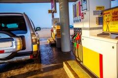 A gasolina de bombeamento abastece-se em um carro em um posto de gasolina trabalhador no elevador de bens; o azul pintou; porta f fotos de stock