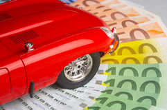 Gasoline. Model of a car lying on the circle of money Royalty Free Stock Image