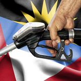 Gasoline consumption concept - Hand holding hose against flag of Antigua and Barbuda royalty free stock photos