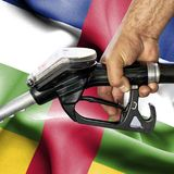 Gasoline consumption concept - Hand holding hose against flag of Central African Republic royalty free stock image