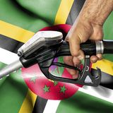 Gasoline consumption concept - Hand holding hose against flag of Dominica royalty free stock photo