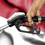 Gasoline consumption concept - Hand holding hose against flag of Indonesia stock photo
