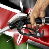 Gasoline consumption concept - Hand holding hose against flag of Kenya royalty free stock images
