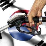 Gasoline consumption concept - Hand holding hose against flag of South Korea stock photo