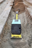 Gasoline or diesel vibratory plate compactor. Vibratory plate compactor compacting sand at road construction site Royalty Free Stock Image
