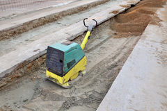Gasoline or diesel vibratory plate compactor. Vibratory plate compactor compacting sand at road construction site Royalty Free Stock Images