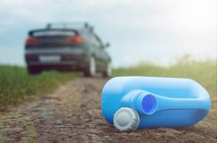Empty fuel canister. Gasoline end concept. Not enough fuel. Empty fuel canister and car on the road background Stock Photo