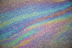 Gasoline flows on the asphalt surface. Iridescent stains of gaso Royalty Free Stock Photo