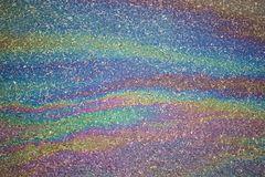 Gasoline flows on the asphalt surface. Iridescent stains of gaso Stock Images