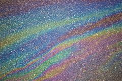 Gasoline flows on the asphalt surface. Iridescent stains of gaso Stock Photo