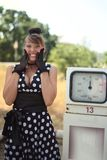 Gasoline has fallen in price!. Very joyful girl costs near a gas station stock photography