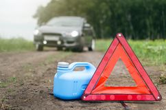 Fuel or gasoline finished. Gasoline has reached a limit concept. Not enough fuel. Red emergency triangle stop sign, empty canister for fuel and car on the road royalty free stock image