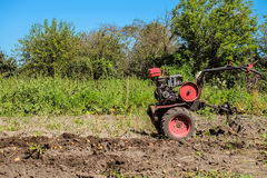 Gasoline motor cultivator near the furrow Royalty Free Stock Image