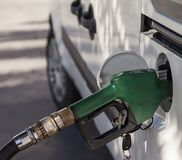 Gasoline  Noose . Isolated. Gasoline pump noose in fuel tank of white car Stock Photo
