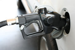 Gasoline nozzle in gas tank. My white SUV guzzling up expensive gasoline Stock Photo