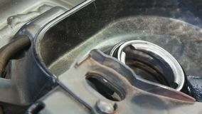 Gasoline pistol is poured into a fuel tank of motorcycle, close up view. stock footage