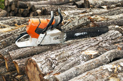 Gasoline powered  chainsaw on pile Royalty Free Stock Photo