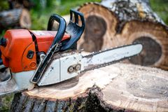 Gasoline powered professional chainsaw on pile of cut wood Stock Photos