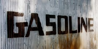 Gasoline Sign left to right. This is a picture of an old sign hand painted on a corrugated steel wall from an old abandoned gas station Royalty Free Stock Photography