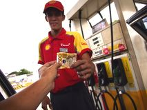 A gasoline station attendant recieves payment from a customer. ANGONO, RIZAL, PHILIPPINES - JULY 29, 2017: A gasoline station attendant recieves payment from a Stock Image