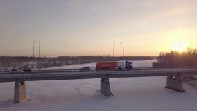 Gasoline truck moving along bridge over frozen river against winter landscape. Gasoline truck moving along bridge over frozen river against beautiful winter stock video