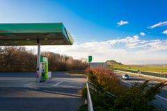 Gasolinera en la autopista Puesta del sol en la gasolinera Coche que viaja en la carretera en la puesta del sol Velocidad máxima  Foto de archivo