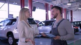 Gasolinera, muchacha feliz del cliente y mecánico hablando de mantenimiento del coche en el taller de reparaciones auto almacen de metraje de vídeo